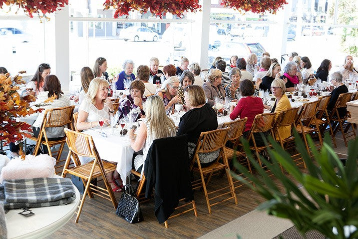 Guests sitting at two long tables enjoying high tea.