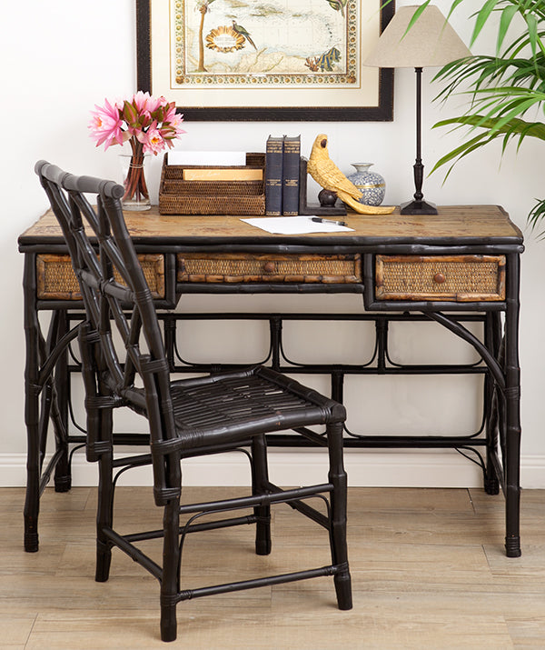 A natural bamboo desk with black chair.