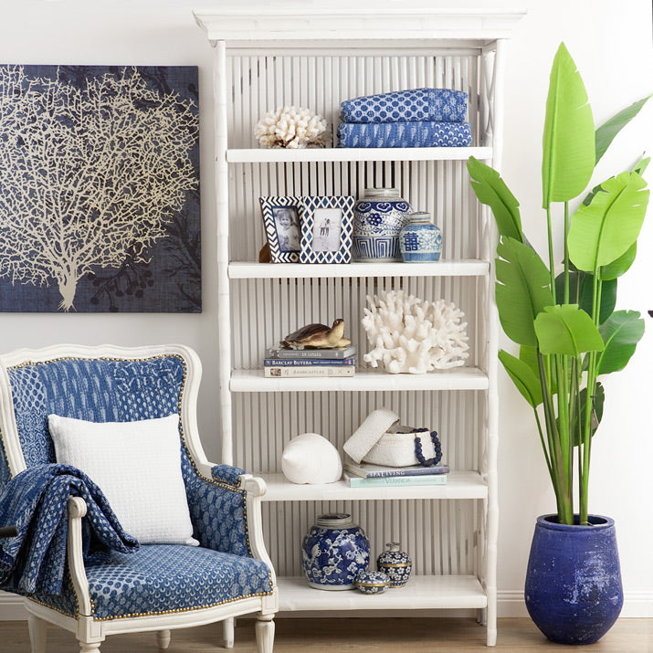 Bookcase with white coral, plams and brass bowls.
