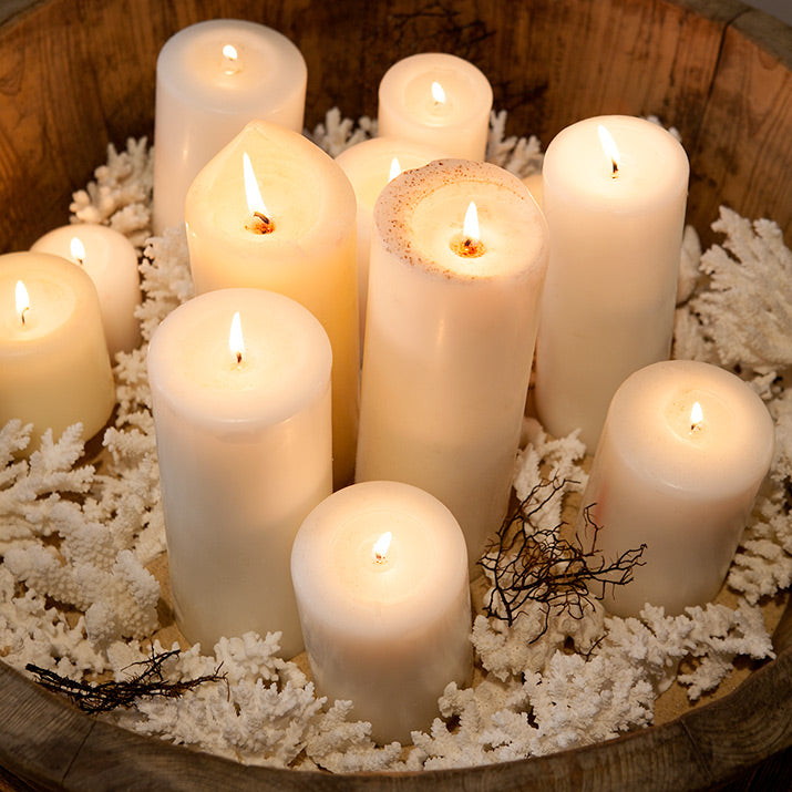 Small white corals styled in a bowl with lots of candles.