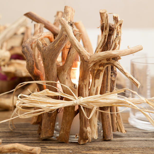 Driftwood tied around an empty glass candle holder.