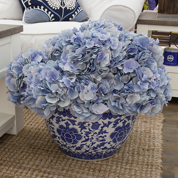 Hydrangeas in a blue and white ceramic planter.