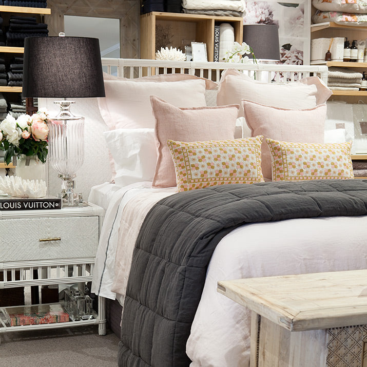 Bed styled with pink and charcoal grey.