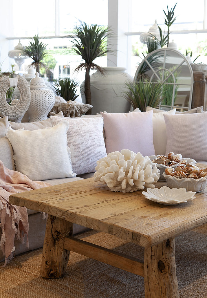 Pale pink cushions on lounge with rustic coffee table.