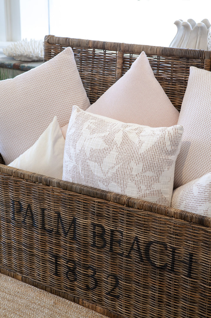 Pale pink cushions in palm beach woven trunk.