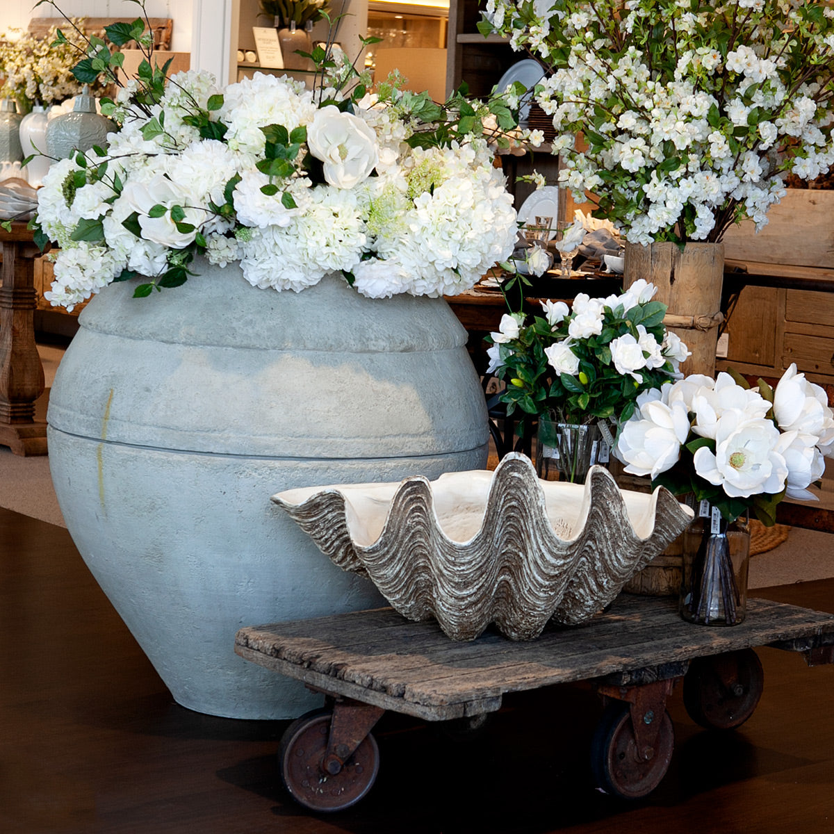 The Poros planter filled with white flowers.