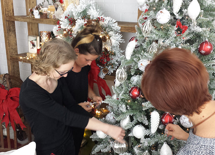 Jan, Emma and Melanie setting up a Christmas tree.
