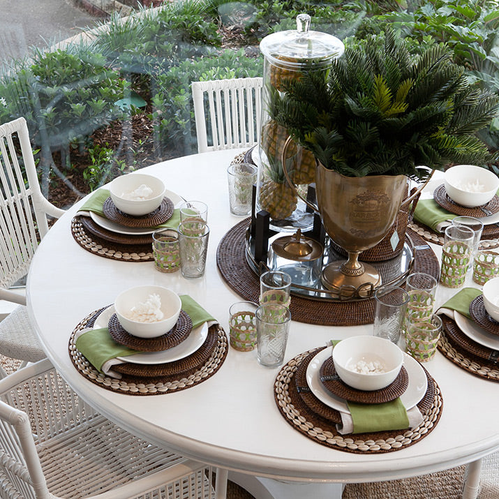 Round white table with brown placemats and green napkins.
