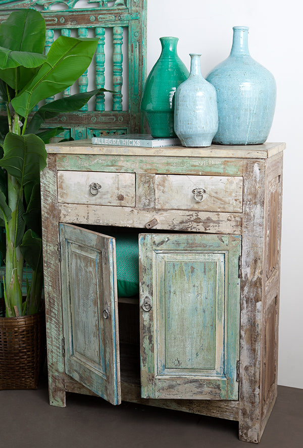 A rustic turquoise cabinet.