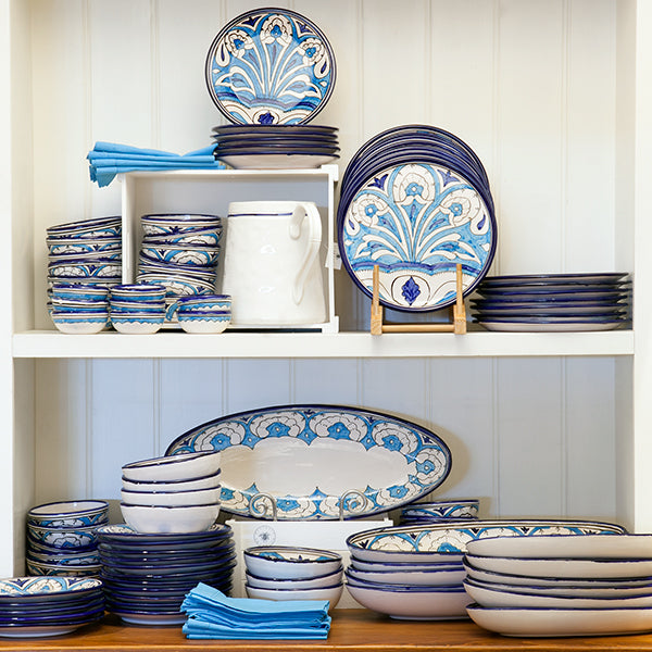 Sol dinnerware in blue displayed in a cabinet.