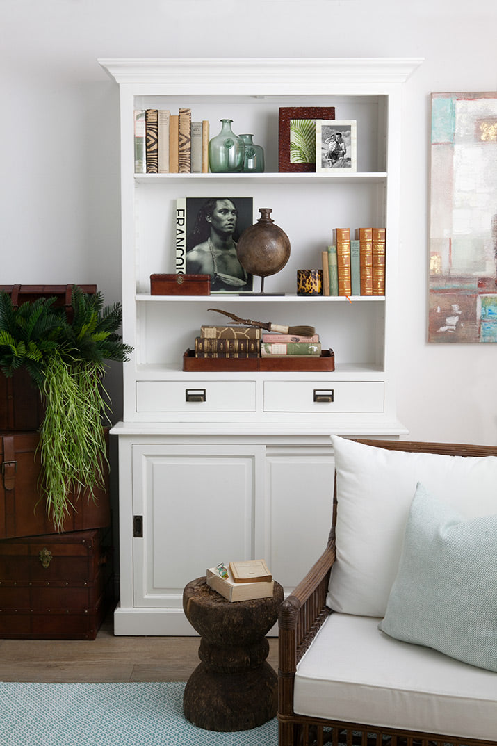 White bookcase styled with leather and aqua tribal accents.