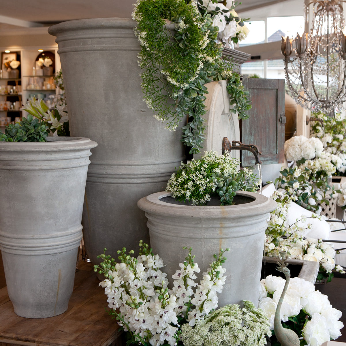 Visconti pots filled with white flowers.