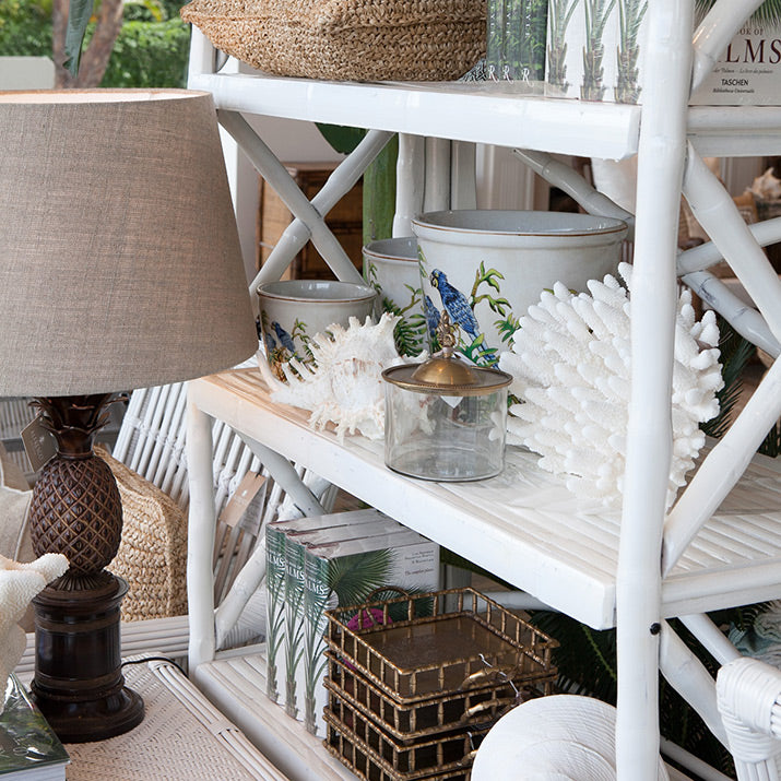 Bamboo bookcase in white styled with coral and greenery.