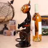 a metal cat wine bottle holder on a kitchen table with a bottle of wine behind it