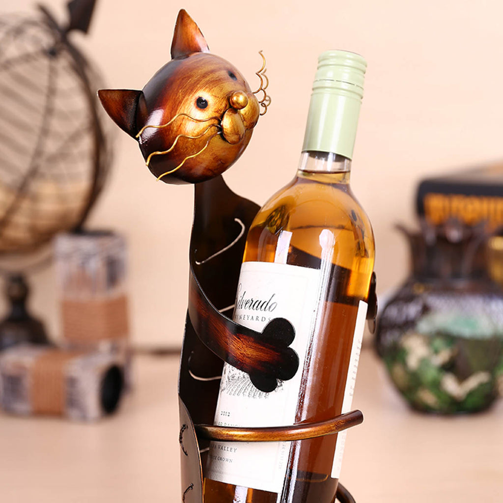 a metal cat wine bottle holder on a kitchen table with a bottle of wine inside of its arms