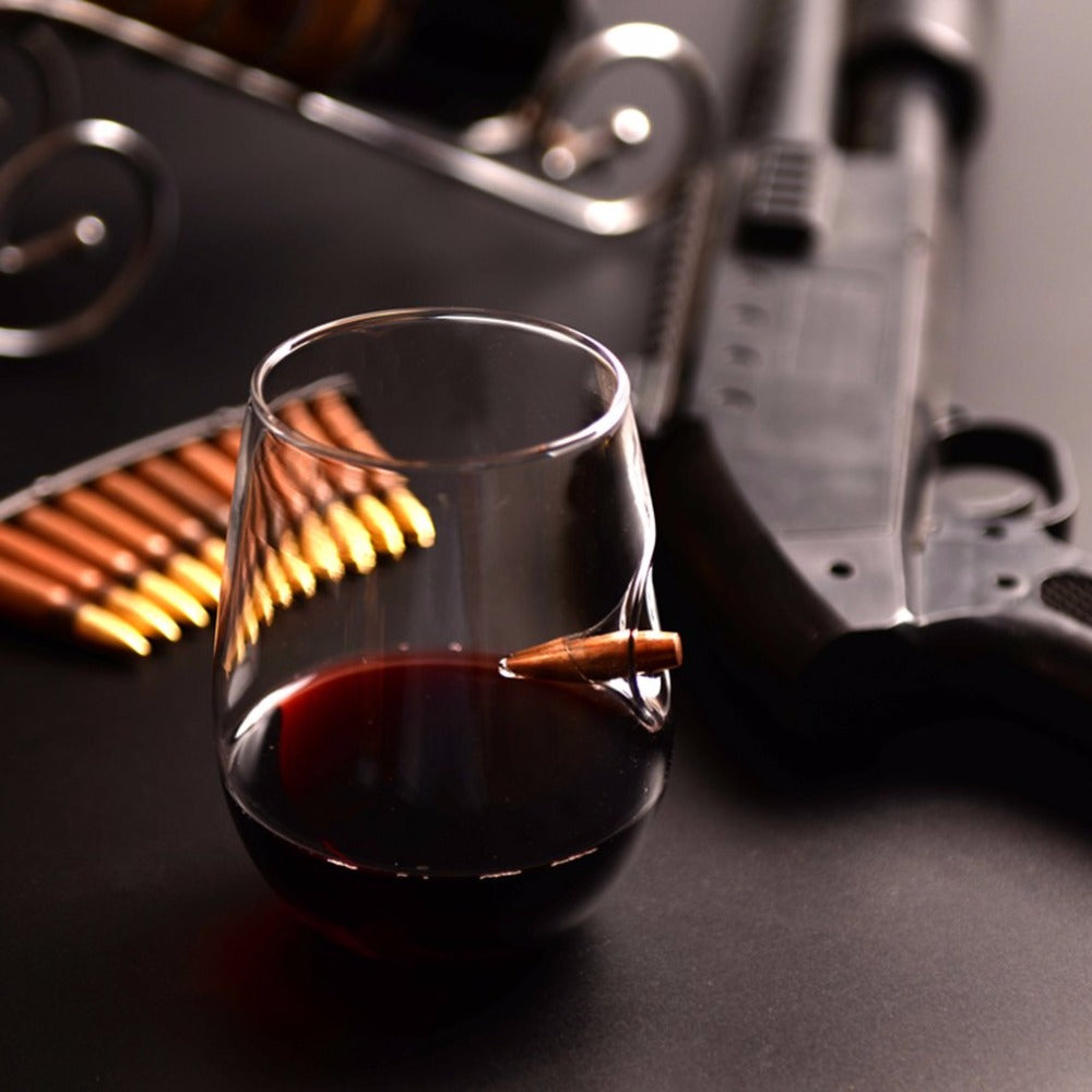an ellipse wine glass with a bullet caught in it on a black table with a shotgun and bullets in the background