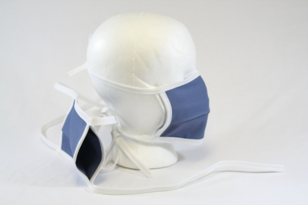 Double layer mask on a mannequin head and another mask off to the side showing the open pocket, which can be used to put in a filter.
