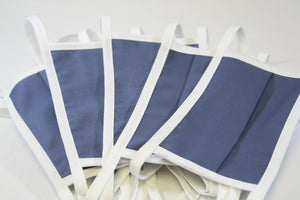 A group of five blue face masks with ties against a white background