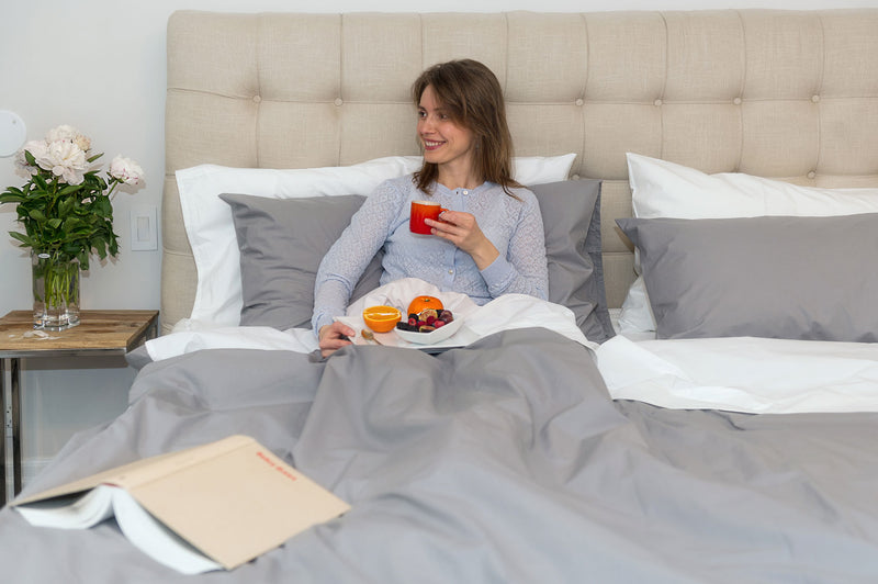 Smiling woman in percale bedding having breakfast