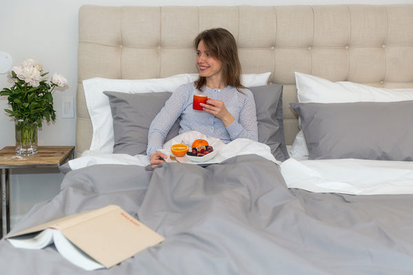 woman enjoying breakfast in premium sheets bed