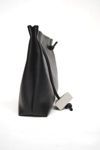 Minimal handbag black faux leather with concrete triangle detail made by Melì
