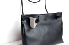 Minimal crossbody bag with pvc handle and concrete detail by Melì