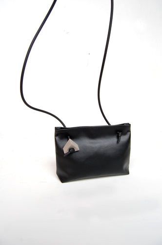 Minimal crossbody bag in black faux leather with concrete detail by Melì