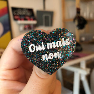 "Broche ""Oui mais non"" en acrylique à paillettes multicolores"
