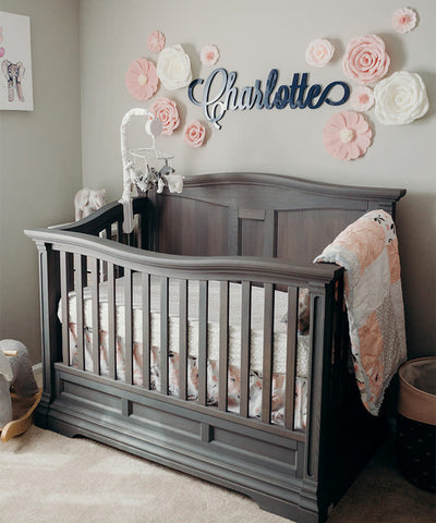 Roses and lettering on the wall under a crib