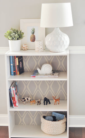 Decorative wallpaper and accessories on a white bookshelf