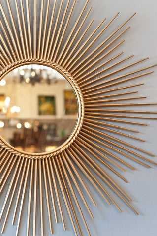 Modern and shiny sun shaped gold mirror on the wall