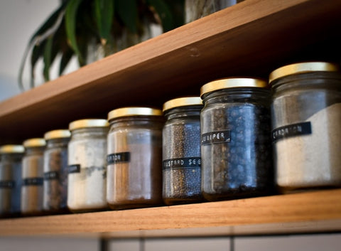 jars of spice labelled and lined up in a row on a shelf