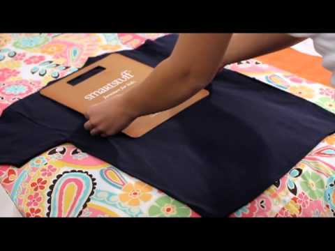 Two hands folding a black t-shirt with a folding board
