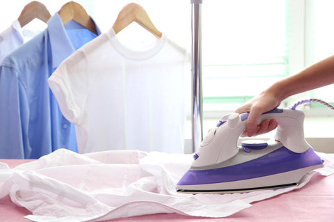 A hand ironing a shirt with three pieces of clothing hanging at the back