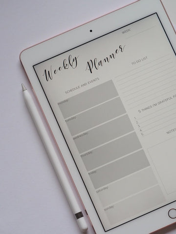iPad with a weekly planner and an Apple Pencil