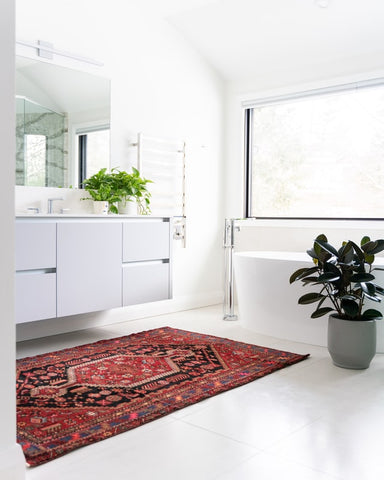 white bathroom with red traditional area rug