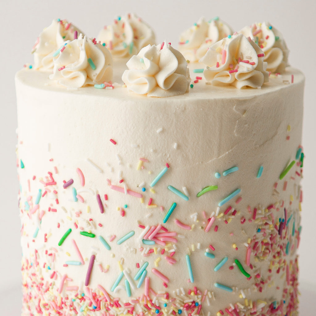 vanilla sponge cake with meringue buttercream, decorated with sprinkles and rosettes