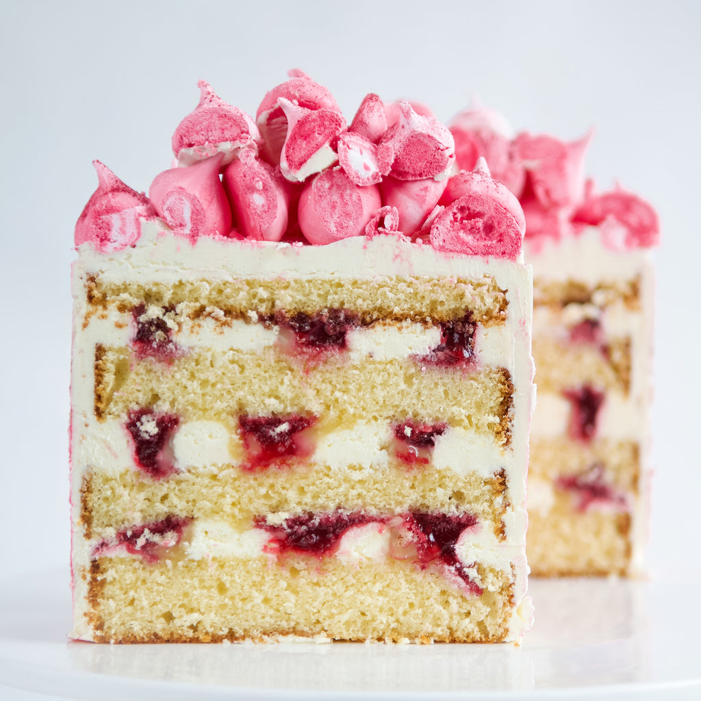 slice of lemon, raspberries and cream layer cake with pink meringue  decoration