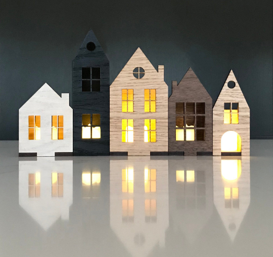 Set of Scaninavian style houses in wood veneer, with battery tea lights glowing in the cut out windows.