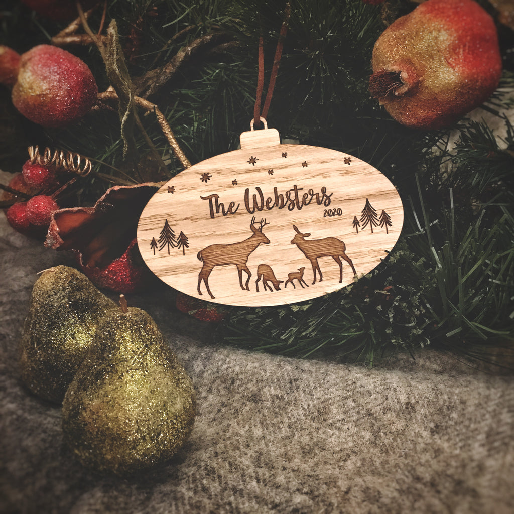 Oval oak bauble engraved with family of deer, Family name and year