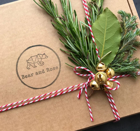 Gift in brown box with bakers twine bells and foliage sprig