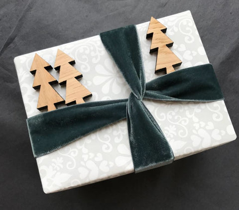 Gift wrapped present with small wooden trees tucked in velvet ribbon