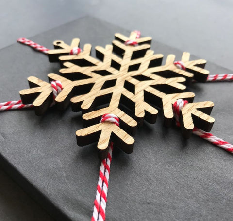 Gift wrapped in tissue with wooden snowflake