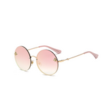 Side view of pink, large circle sunglasses, with mirror lenses and bee detail on the lenses.