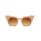 Front view of nude, super cat eye sunglasses, with brown lenses.