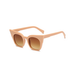 Side view of nude, super cat eye sunglasses, with brown lenses.