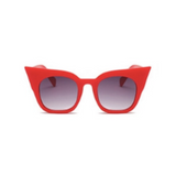Front view of red, super cat eye sunglasses, with black gradient lenses.