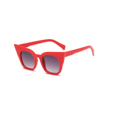 Side view of red, super cat eye sunglasses, with black gradient lenses.
