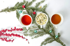 Three tea gift set including Coconut Chai, Earl Grey, and Chrysanthemum. Next to wreaths and berries