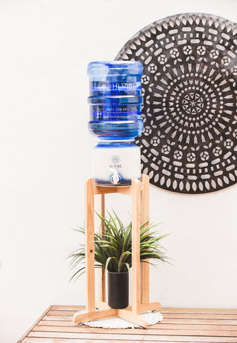 Beautiful Timber Stand with Hi Vibe Ceramic placed on top, water on ceramic.  litre water bottles next to the stand. A plant is on the base of the stand with a beautiful mandala in the background.